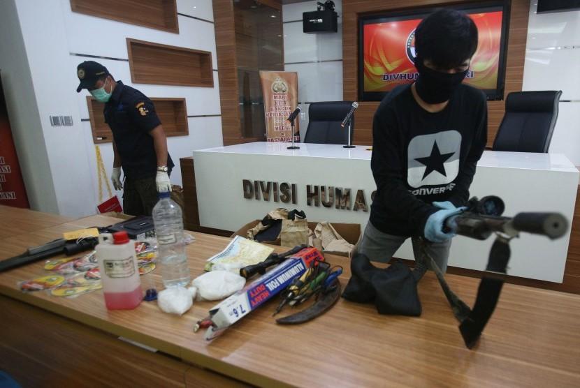 Petugas kepolisian menunjukkan sejumlah barang bukti yang diamankan saat penangkapan para terduga teroris yang berada di Bekasi, di Mabes Polri, Jakarta, Kamis (15/12).