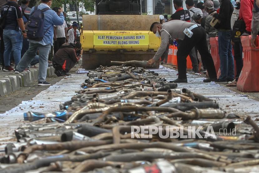Petugas Kepolisian Satlantas Polrestabes Medan menggunakan alat berat disaat memusnahkan barang bukti tangkapan knalpot blong (bising) di Medan, Sumatra Utara, beberapa waktu lalu.