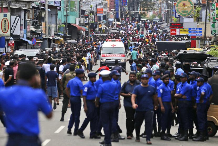Petugas kepolisian Sri Lanka membuka jalan ketika sebuah mobil ambulans melaju dengan membawa korban ledakan Gereja di Kolombo, Sri Lanka, Ahad (21/4/2019).