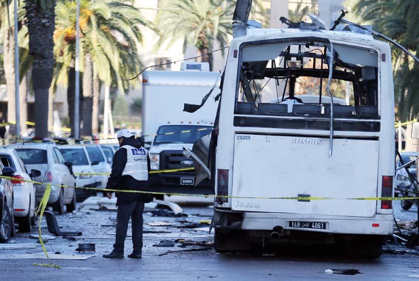 Petugas kepolisian Tunisia memeriksa lokasi dimana sebuah bus hancur diserang aksi bom bunuh diri di Tunis, Tunisia, Rabu (25/11).