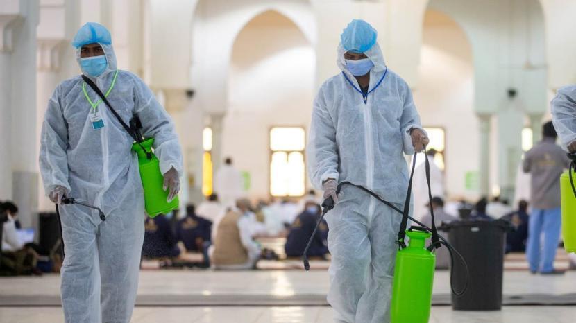 Vaksin Covid-19 Wajib Bagi Petugas Haji dan Umroh Saudi. Petugas kesehatan Arab Saudi dengan memakai APD mendesinfeksi lantai Masjid Namira di Arafah, Makkah saat musim haji 30 Juli 2020. Desinfeksi demi mencegah penyebaran virus Covid-19.