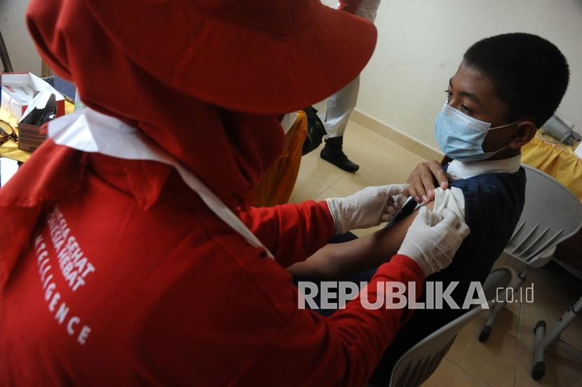 Petugas kesehatan bersiap menyuntikkan vaksin COVID-19 ke salah satu pelajar pada vaksinasi massal di SMP Negeri 53 Palembang, Sumsel, Selasa (19/10/2021). (Ilustrasi)