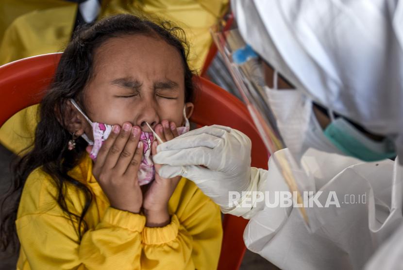 Petugas kesehatan dari Puskesmas Cikole mengambil sampel lendir dari seorang anak saat kegiatan rapid test antigen di halaman Kantor Kepala Desa Cibogo, Desa Cibogo, Kecamatan Lembang, Kabupaten Bandung Barat, Selasa (8/6).