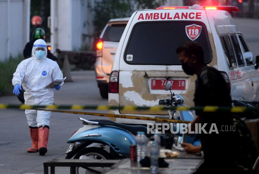 Petugas kesehatan dengan menggunakan baju hazmat melapor di pos masuk saat mengantarkan pasien Covid-19 di Rumah Sakit Darurat Covid-19 Wisma Atlet, Jakarta, Ahad (13/6).