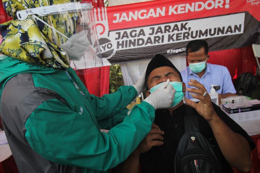 Petugas kesehatan melakukan tes cepat antigen kepada pemudik saat penyekatan larangan mudik Lebaran 2021 di akses keluar Jembatan Suramadu, Surabaya, Jawa Timur, Sabtu (15/5/2021). Sejumlah pemudik dari Pulau Madura menuju Surabaya yang terjaring dalam penyekatan tersebut dilakukan tes cepat antigen sebagai upaya pencegahan penularan COVID-19.