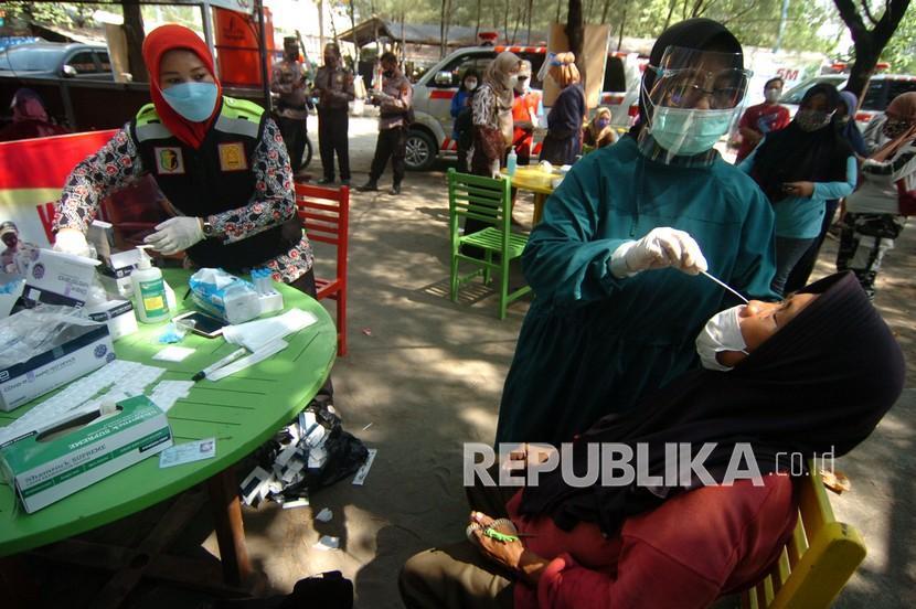 Petugas kesehatan melakukan tes usap antigen kepada pedagang di Obyek Wisata Pantai Alam Indah, Tegal, Jawa Tengah, Sabtu (12/6/2021). Tes usap antigen dan penyuntikan vaksinasi kepada pedagang dan tukang parkir tempat wisata oleh Dinas Kesehatan dan TNI/Polri tersebut guna pengendalian penyebaran COVID-19 di ruang publik menyusul semakin meningkatnya kasus COVID-19 di Kota Tegal.