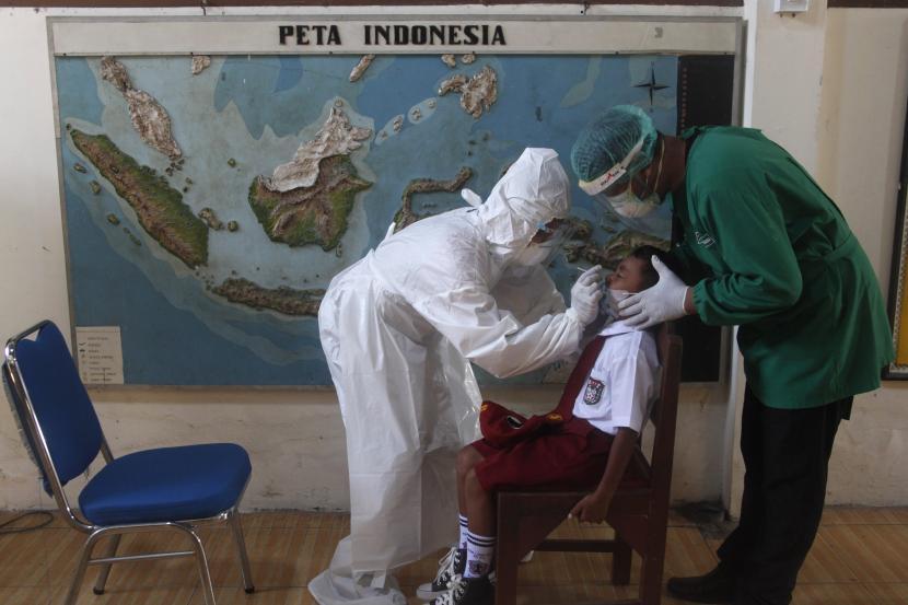 Petugas kesehatan melakukan tes usap antigen kepada siswa di SDN 40 Laweyan Solo, Jawa Tengah, Senin (27/9/2021).