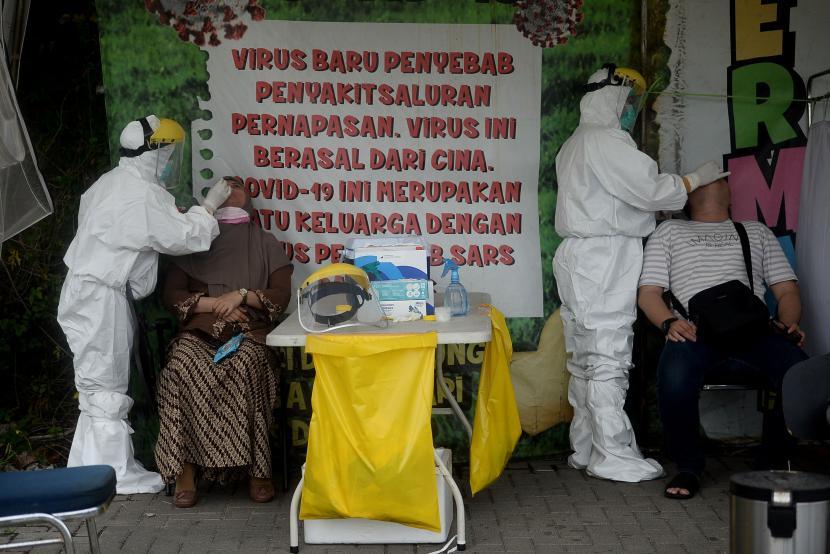 Petugas kesehatan melakukan tes usap PCR COVID-19 kepada warga di Lokasi Swab PCR Puskesmas Kecamatan Gambir, Jakarta.