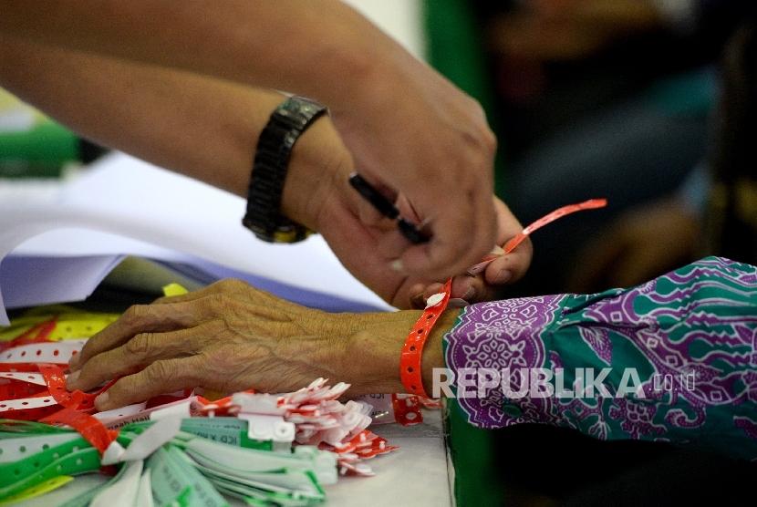 Petugas kesehatan memasang gelang kepada jamaah calon haji Kloter 25 di Embarkasi DKI Jakarta, Pondok Gede, Jakarta, Selasa (8/8)