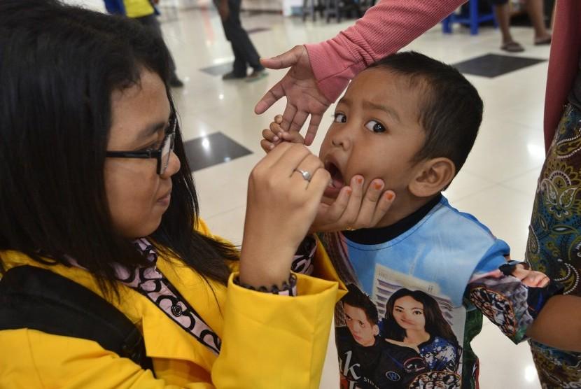 Petugas kesehatan memberikan imunisasi Polio kepada seorang anak di salah satu pusat perbelanjaan, Abepura, Kota Jayapura, Papua, Senin (14/3).