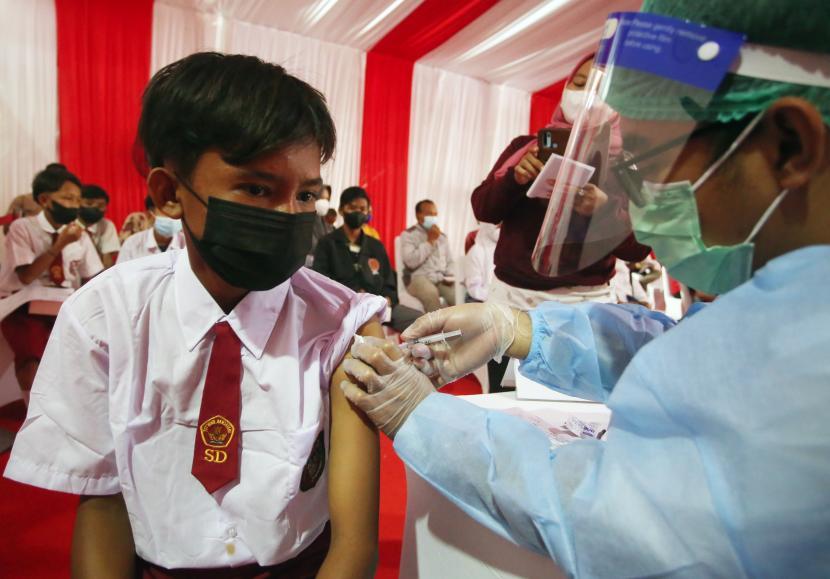 Petugas kesehatan menyuntikan vaksin Covid-19 ke seorang pelajar SD saat vaksinasi Covid-19 Massal Alumni Akpol 1997 di Polres Bandara Soekarno Hatta, Tangerang, Banten, Senin (20/9/2021).