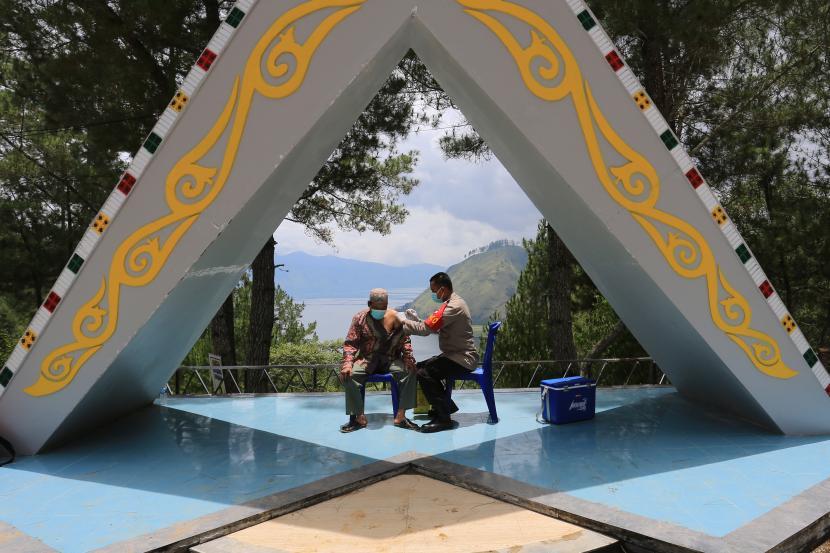 Petugas kesehatan menyuntikkan vaksin Covid-19 kepada pengunjung di lokasi wisata Bur Telege, Desa Hakim Bale Bujang, Lut Tawar, Aceh Tengah, Aceh, Minggu (19/9/2021). Vaksinasi untuk daerah-daerah di luar Jawa-Bali terus ditingkatkan agar bisa menekan kasus Covid.