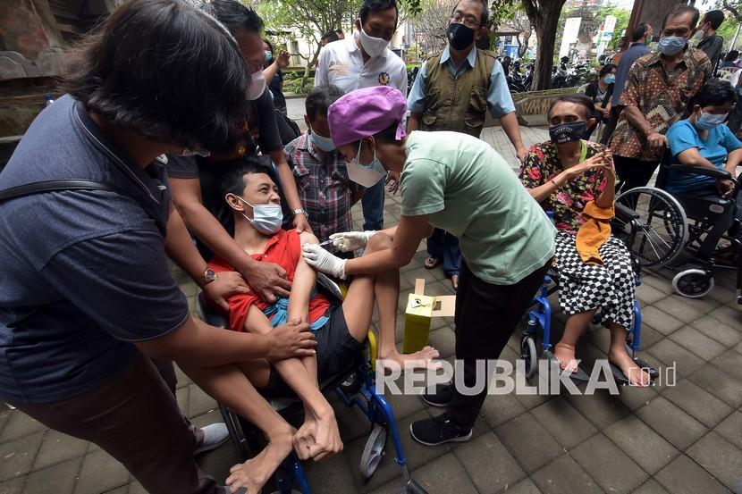 Petugas kesehatan menyuntikkan vaksin COVID-19 kepada penyandang tuna daksa di Rumah Bisabillitas, Denpasar, Bali, Ahad (9/5/2021). Pemerintah Kota Denpasar menggelar vaksinasi bagi penyandang disabilitas yang diikuti 384 orang untuk pencegahan penyebaran COVID-19 sekaligus percepatan Bali bebas COVID-19.