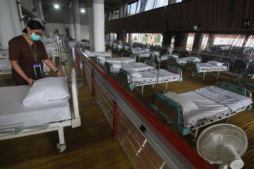 Petugas kesehatan merapikan tempat tidur pasien di Rumah Sakit Lapangan Tembak (RSLT) di kawasan Kedung Cowek, Surabaya, Jawa Timur, Sabtu (10/7/2021). Pemerintah Kota (Pemkot) Surabaya mengubah gedung lapangan tembak itu menjadi Rumah Sakit Lapangan Tembak (RSLT) khusus pasien COVID-19 dengan daya tampung seribu tempat tidur pasien namun untuk tahap awal tersedia 400 tempat tidur pasien.