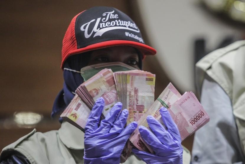 Petugas KPK menunjukkan barang bukti berupa uang sebanyak Rp240 juta hasil OTT DPRD Kalteng saat konferensi pers di gedung KPK, Jakarta, Sabtu (27/10/2018).
