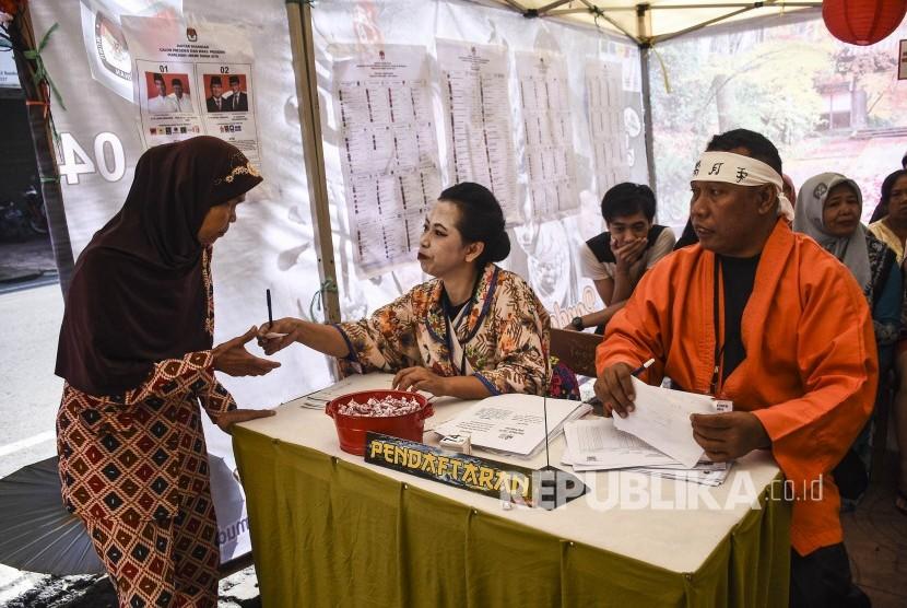 Petugas KPPS membantu warga yang akan memberikan hak suaranya di TPS 004 Pemilu 2019 di Kelurahan Cibadak, Kecamatan Astanaanyar, Kota Bandung, Rabu (17/4).