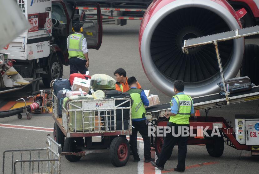 Petugas masukan barang milik penumpang ke bagasi pesawat di Bandara Internasional Soekarno,-Hatta, Tanggerang,Banten, Kamis (7/2). Kementerian Perhubungan (Kemenhub) tengah merumuskan aturan mengenai penetapan tarif bagasi untuk maskapai Low Cost Carrier (LCC). Upaya ini dilakukan sebagai bentuk tindak lanjut perlindungan para penumpang dan bisnis maskapai.
