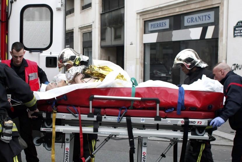 Petugas medik membawa korban yang terluka saat penembakan kantor majalah Charlie Hebdo di Paris, Prancis.