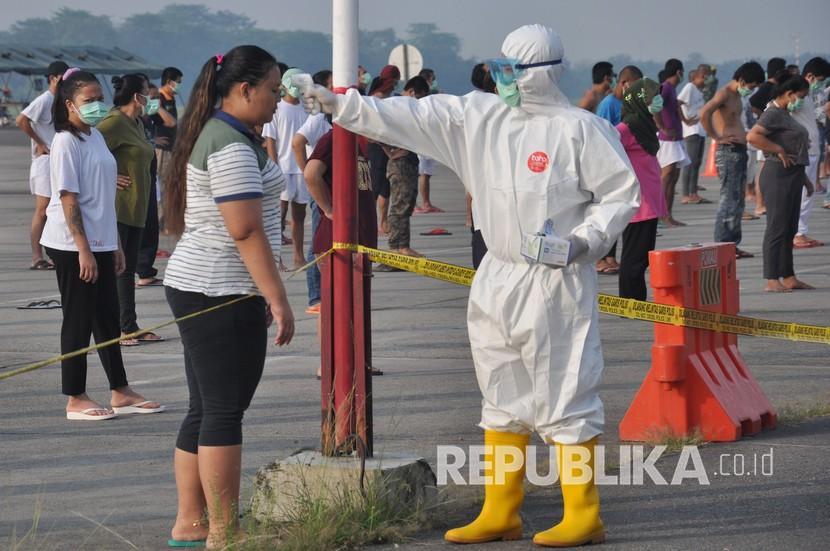 Petugas medis Gugus Tugas Percepatan Penanganan COVID-19 Sumut memeriksa suhu tubuh seorang Tenaga Kerja Indonesia (TKI) asal Malaysia ketika akan mengikuti senam dan berjemur di bawah sinar matahari saat menjalani karantina di Pangkalan Udara Militer (Lanud) Soewondo Medan, Sumatera Utara, Sabtu (11/4/2020). Ilustrasi.