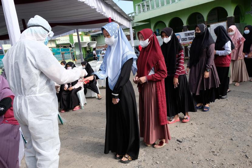 Petugas medis memeriksa suhu badan santri saat vaksinasi massal di Pondok Pesantren Al Fatah Banjarnegara, Jawa Tengah, Minggu (25/7/2021). Vaksinasi massal bagi santri tersebut diselanggarakan oleh Badan Intelejen Negara bekerjasama dengan Satgas Penanggulangan COVID-19 Kabupaten Banjarnegara