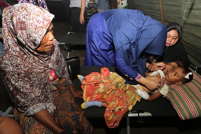 Petugas medis menangani seorang anak korban gempa di Rumah Sakit Umum Daerah (RSUD) Tgk Chik Ditiro Sigli di Pidie, Aceh, Rabu (7/12).