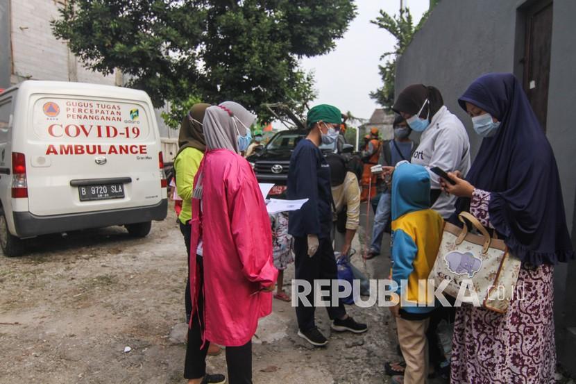Petugas medis mendata warga yang akan dibawa ke Wisma Atlet di Jalan As-Syafiiyah, Cipayung, Jakarta, Jumat (21/5/2021). Klaster halal bihalal di Cipayung bertambah sebanyak 32 orang, dari 51 orang menjadi 83 orang terpapar COVID-19 perhari ini dan sebanyak 17 orang bergejala ringan dibawa ke Wisma Atlet, tiga orang bergejala sedang dibawa ke RSUD Ciracas dan 12 orang OTG isolasi mandiri.