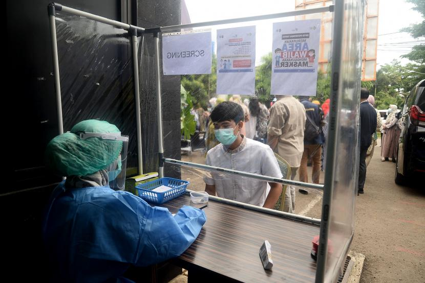 Petugas medis menscreening warga saat proses simulasi uji coba vaksinasi Covid-19 di Puskesmas Tapos, Depok, Jawa Barat.