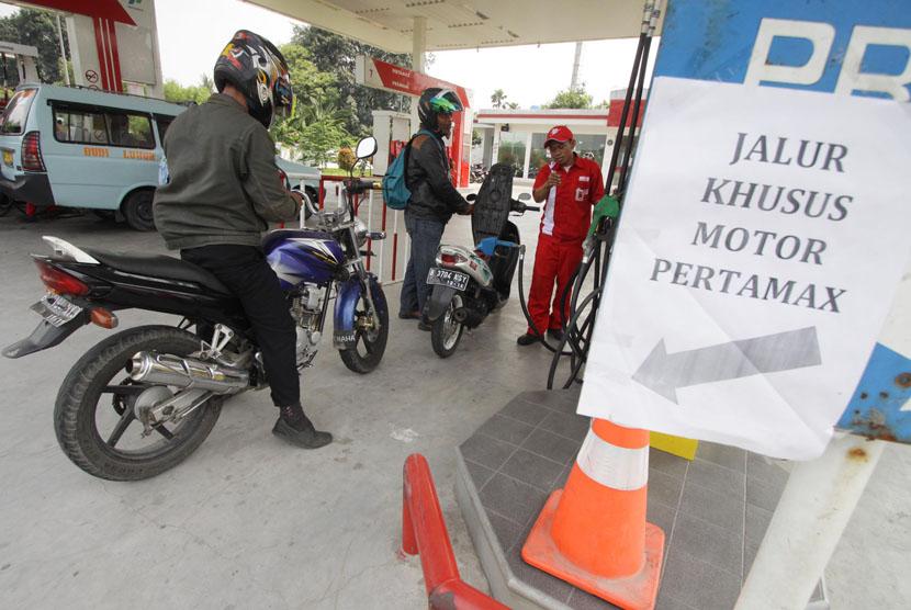 Petugas melakukan pengisian bahan bakar Pertamax di SPBU Kalideres, Jakarta Barat, Kamis (4/12).