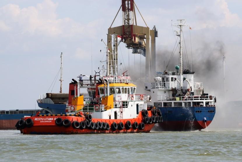 Petugas membantu memadamkan api di kapal yang terbakar (ilustrasi)