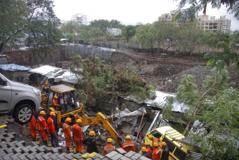 Petugas melakukan upaya evakuasi terhadap korban yang terjebak reruntuhan tembok di Pune, India.