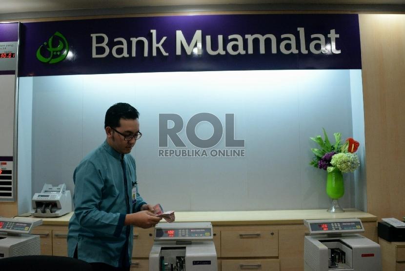 Petugas melayani nasabah di salah satu kantor cabang Bank Muamalat, Jakarta, Selasa (10/3).
