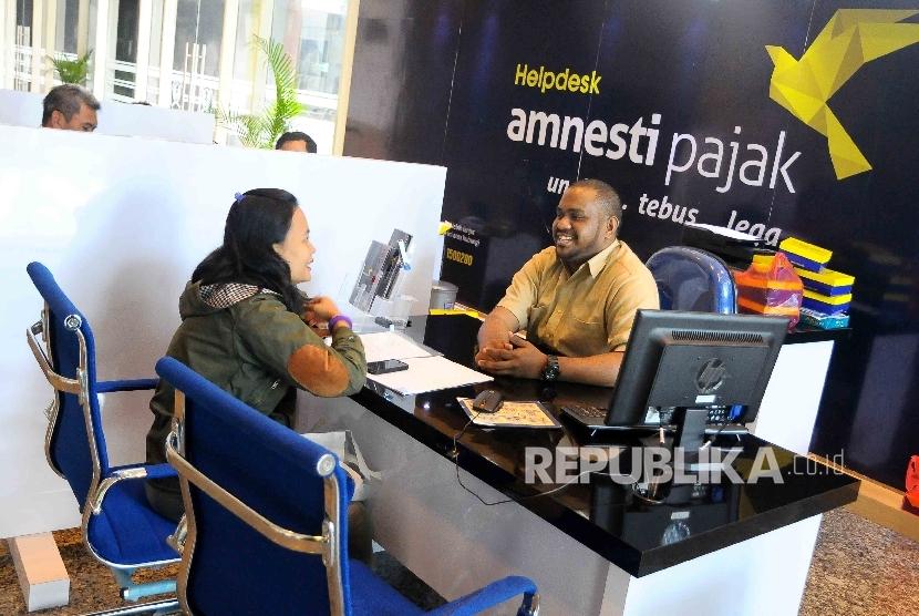 Petugas melayani wajib pajak yang ingin memperoleh informasi mengenai kebijakan amnesti pajak (tax amnesty) di Help Desk, di Gedung Direktorat Jenderal Pajak, Jakarta Pusat, Kamis (8/12).