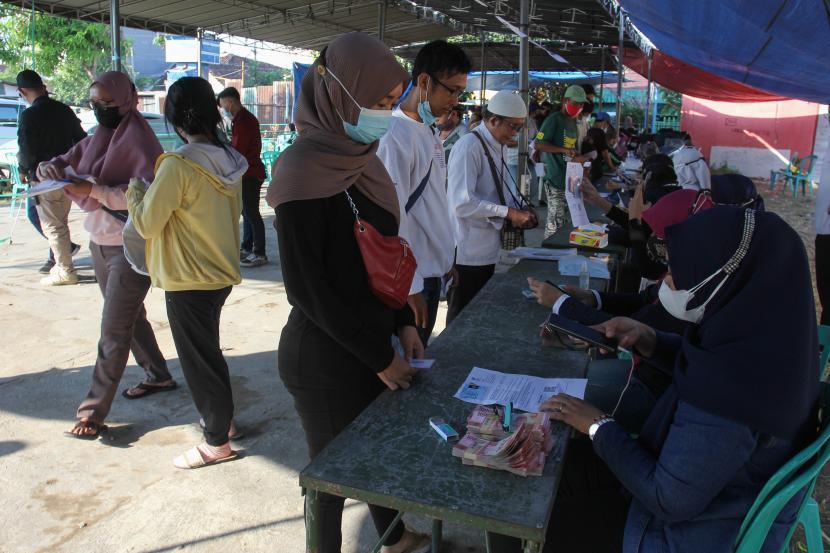 Petugas melayani warga penerima Bantuan Sosial Tunai (BST) di Surabaya, Jawa Timur, Ahad (25/7/2021). Kantor Pos Surabaya menyalurkan BST program pemerintah tersebut kepada 172. 870 Keluarga Penerima Manfaat (KPM) di Surabaya yang dilakukan secara bertahap.