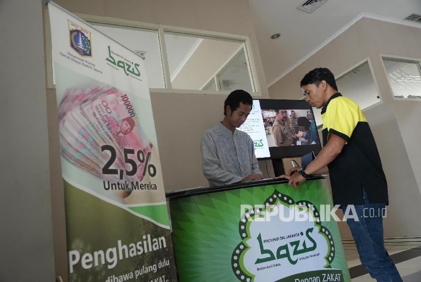 Petugas melayani warga yang akan berzakat di Unit Pengumpul Zakat (UPZ) Bazis DKI Jakarta, Selasa (27/12).