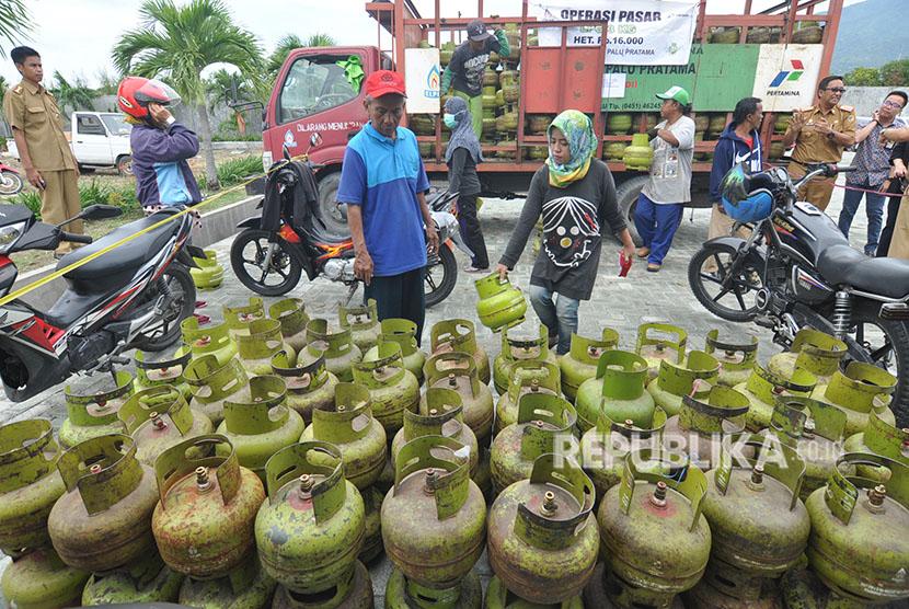 Petugas melayani warga yang membeli elpiji tiga kilogram bersubsidi dalam operasi pasar (OP) yang digelar di Palu, Sulawesi Tengah, Selasa (5/6).