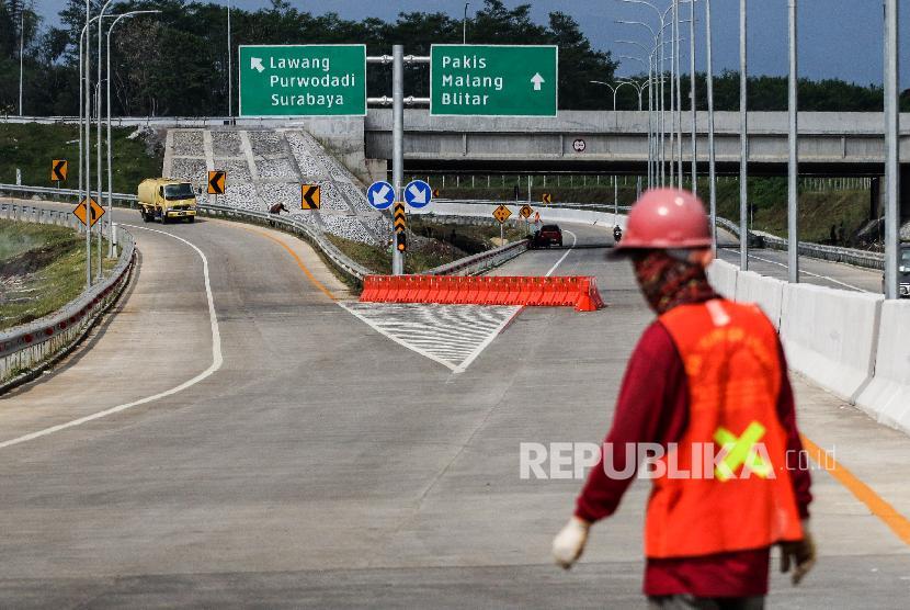 Petugas melintas di tol Singosari yang belum beroperasi di Malang, Jawa Timur, Minggu (12/5/2019). Ruas Tol Pandaan-Malang seksi I-III dari Pandaan-Singosari sepanjang 31 Km itu diharapkan akan memperlancar arus mudik Lebaran 2019 di Jawa Timur.