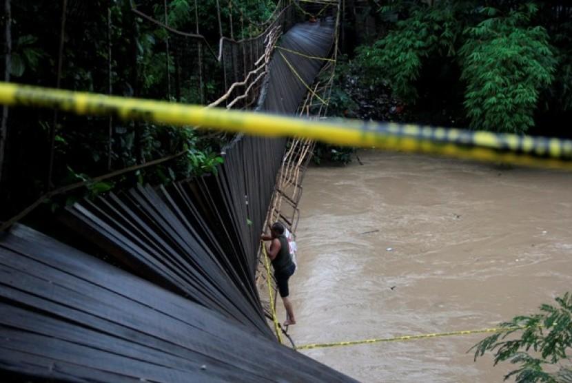 Petugas memasang garis polisi di jembatan gantung yang roboh di Kampung Pekarungan, Serang, Banten, Selasa (21/1).