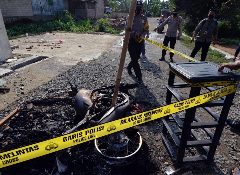 Petugas memasang garis polisi di puing kendaraan dinas yang di bakar oleh massa di Mapolsek Candipuro, Lampung Selatan, Lampung, Rabu (19/5/2021). Aksi pembakaran Mapolsek Candipuro oleh massa yang terjadi pada Selasa (18/05/2021) malam diduga dipicu kekesalan warga atas maraknya kasus kriminal pencurian dengan kekerasan atau begal di wilayah hukum Polsek tersebut yang tidak terungkap.