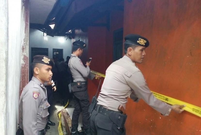Petugas memasang garis polisi untuk menyegel rumah terduga teroris setelah penangkapan pada Kamis (15/12) di Kota Tasikmalaya, Jawa Barat