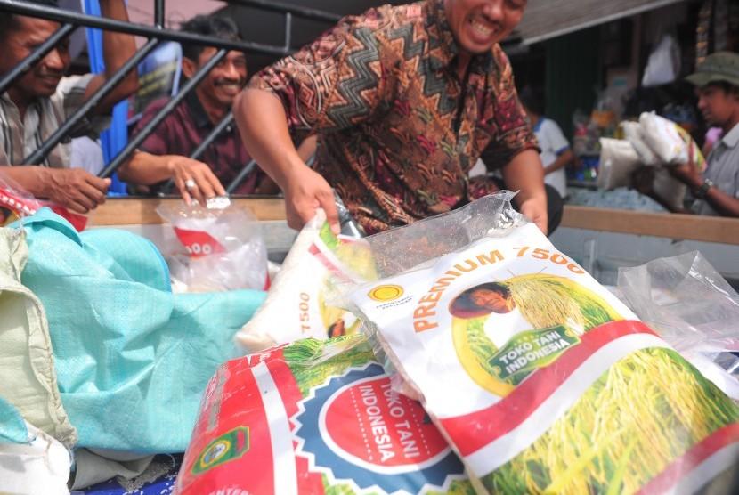 Petugas memasok permintaan produk beras lokal Sumatera Selatan kepada sejumlah pedagang di Toko Tani Pasar Gubah Palembang, Senin (28/3).