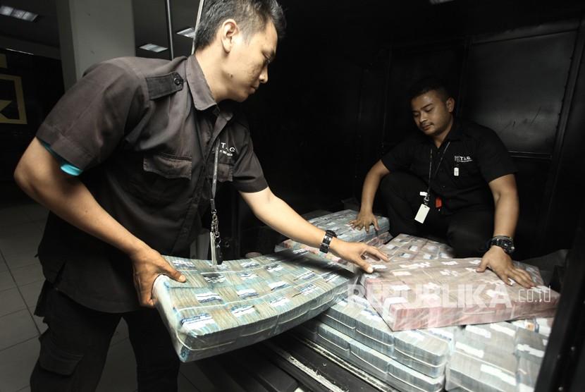 Petugas memasukan uang tunai ke dalam mobil untuk didistribusikan melalui kantor cabang dan mesin ATM, di cash pooling Plaza Mandiri, Jakarta, Selasa (19/12).