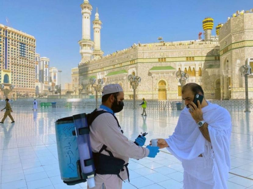Petugas membagikan air zamzam kepada jamaah umroh di Masjidil Haram. Petugas membawa wadah silindris berisi air Zamzam. Tindakan itu untuk membendung penyebaran virus corona (Covid-19).
