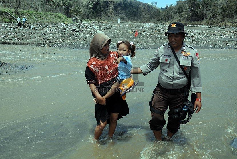 Petugas membantu mengevakuasi warga warga Desa Pandansari yang terputus akses jalannya akibat lahar dingin Gunung Kelud di Kecamatan Ngantang, Malang, Jawa Timur, Kamis (20/2).