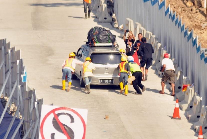 Petugas membantu sebuah kendaraan pemudik yang tidak kuat mendaki tanjakan darurat Kali Kenteng.