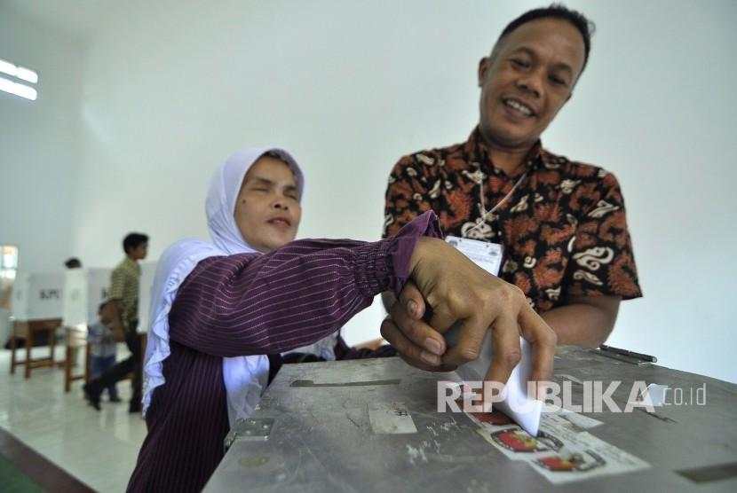 Petugas membantu seorang difabel tunanetra memasukan surat suara ke dalam kotak suara di Tempat Pemungutan Suara (Ilustrasi).