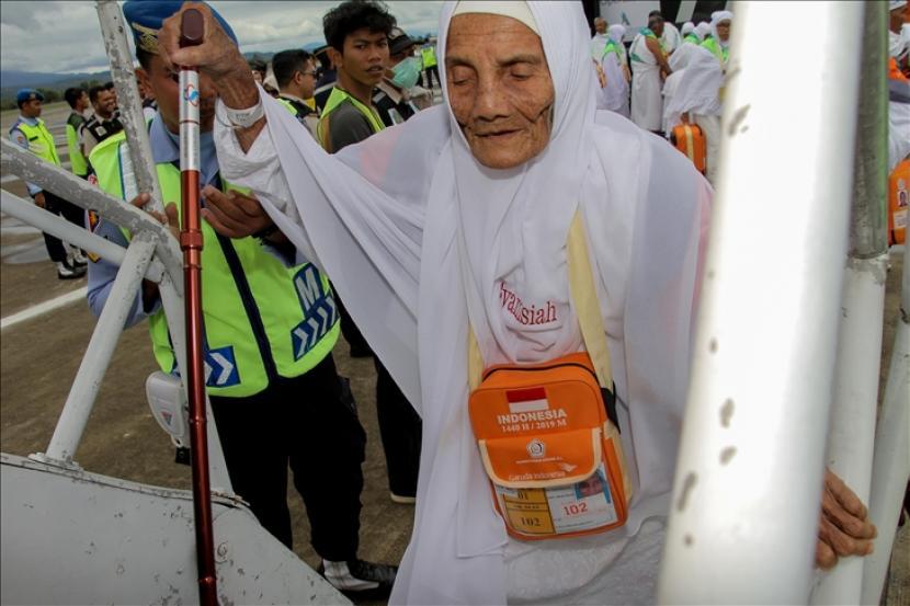 Petugas membantu seorang jamaah calon haji saat menaiki pesawat di Bandara Sultan Iskandar Muda, Aceh Besar, Aceh, Indonesia, Sabtu 20 Juni 2019. Panitia Penyelenggara Ibadah Haji (PPIH) Aceh membagi 12 kelompok terbang, sebanyak 393 JCH kloter 1 diberangkatkan dari Embarkasi Aceh.