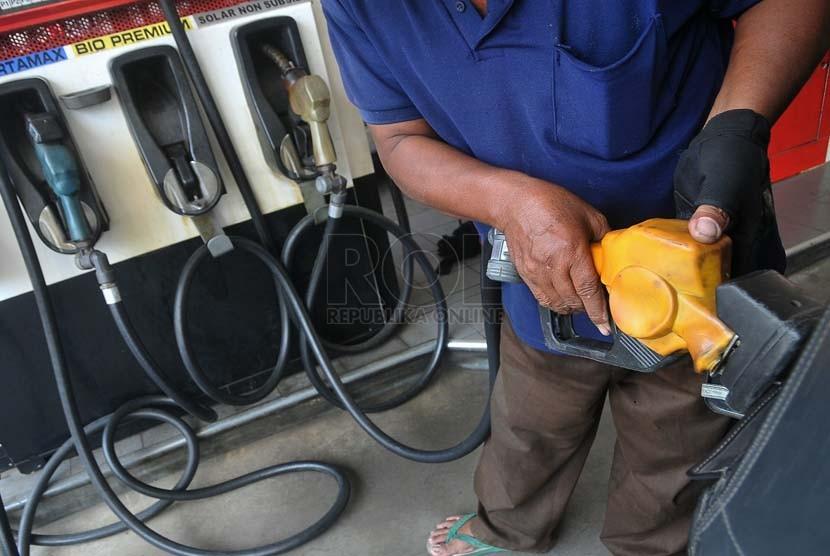 Petugas membantu warga mengisi bahan bakar minyak (BBM) jenis premium di SPBU Jakarta,Selasa (23/9).(Republika/Prayogi)