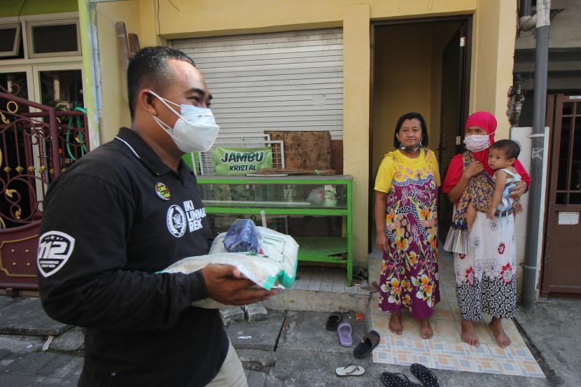 Petugas membawa bantuan beras untuk dibagikan kepada warga di Surabaya, Jawa Timur, Rabu (28/7/2021). Pembagian beras dari Kementerian Sosial kepada penerima bantuan tersebut untuk meringankan beban mereka yang terdampak oleh pandemi COVID-19.
