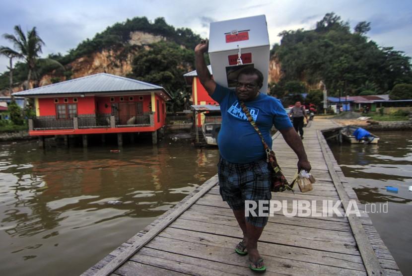 Petugas membawa kotak suara ketika melakukan pendistribusian logistik Pemilu 2019 di Kampung Kayu Pulo, Jayapura, Papua, Selasa (16/4/2019).