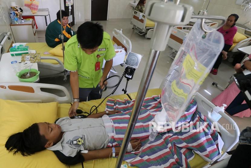 Petugas memberikan penanganan medis kepada pasien penderita Demam Berdarah Dengue (DBD).